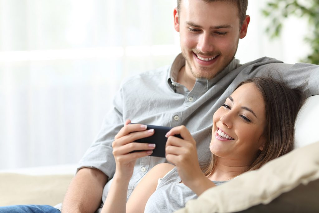 Couple enjoying media content in a smart phone